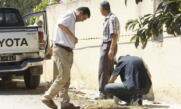 Forensic inspectors examine the area near the car of Tunisian