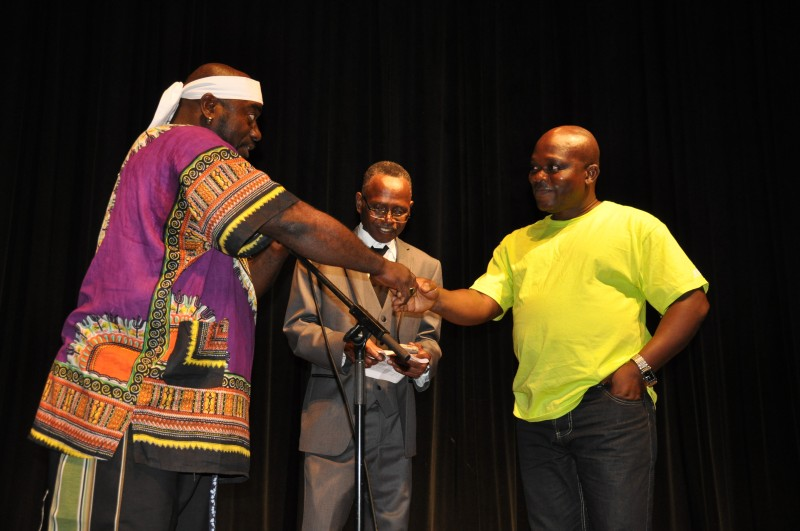 Francis Nimely Vinney Napla, (l) Artistic Director, Liberian National Cultural Ambassadors, greets Andrew Tehmeh (r), Deputy culture minister. Photo: Issa Mansaray/The AfricaPaper