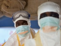 DON'T TOUCH Health workers in protective gear prepare to see patients at the Ebola-treatment center in the courtyard of Donka hospital, in Conakry, Guinea.