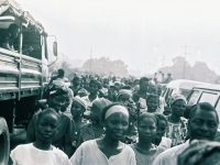 """Thousands of Liberians trapped in then """"Greater Liberia"""" flocked into the Mount Barclay buffer zone on the out-sketch of Monrovia in 1991. The await the official re-opening of the main Monrovia Kakata-Gbarnga Highways that connects the rest of the country to the capital. While some came eager to enter Monrovia to search for lost relatives separated the NPFL-AFL war into its second year. Many too advantage of this single act by the faction to seek respite from harassment and brutality by the NPFL. Others escape the faction's territories known as """"Taylor Land."""" Former NPFL spokesperson-later Defense Minister Jucontee Thomas Woewiyu led a high-powered NPFL delegation to this elaborate event, accompanied by other NPFL officials including lawyer Francis Garlawolo, NPFL chief of staff Gen. Isaac Musa and the front's information minister, Joseph Wolobah Mulbah(not in this photograph). Photo: James K. Fasuekoi/The AfricaPaper"""