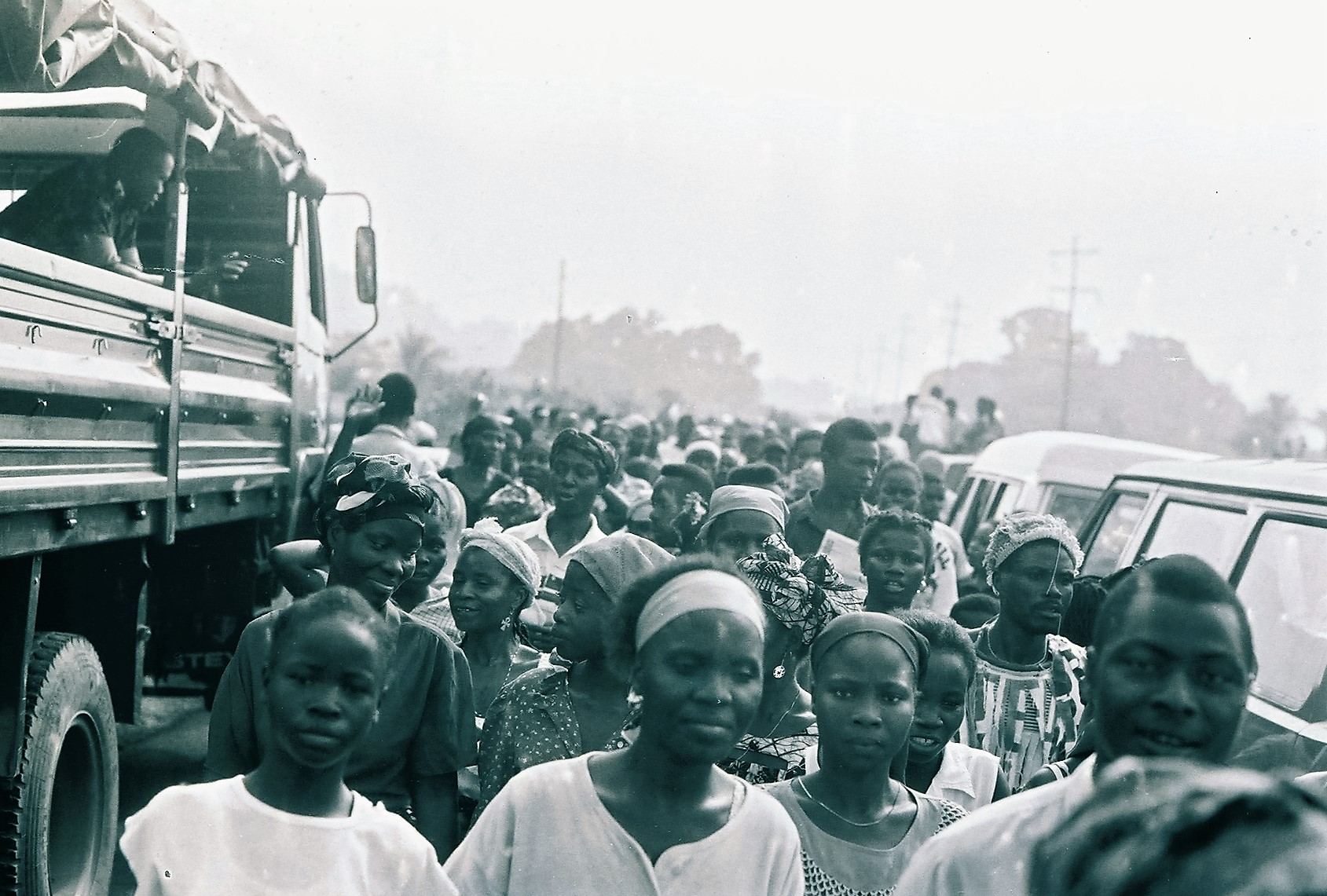 "Thousands of Liberians trapped in then ""Greater Liberia"" flocked into the Mount Barclay buffer zone on the out-sketch of Monrovia in 1991. The await the official re-opening of the main Monrovia Kakata-Gbarnga Highways that connects the rest of the country to the capital. While some came eager to enter Monrovia to search for lost relatives separated the NPFL-AFL war into its second year. Many too advantage of this single act by the faction to seek respite from harassment and brutality by the NPFL. Others escape the faction's territories known as ""Taylor Land."" Former NPFL spokesperson-later Defense Minister Jucontee Thomas Woewiyu led a high-powered NPFL delegation to this elaborate event, accompanied by other NPFL officials including lawyer Francis Garlawolo, NPFL chief of staff Gen. Isaac Musa and the front's information minister, Joseph Wolobah Mulbah(not in this photograph). Photo: James K. Fasuekoi/The AfricaPaper"