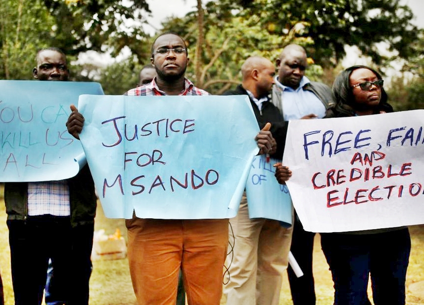 Residents from late Msando village carry placards in protest of unfinished probe investigations